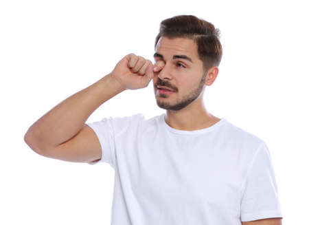 Young man rubbing eye on white background. Annoying itch