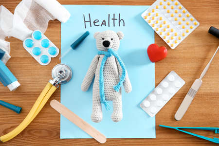 Flat lay composition with toy bear and medical items on wooden background. Childrens doctor