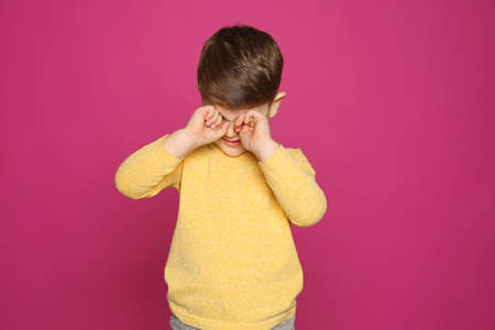 Little boy rubbing face on color background. Annoying itch Stock Photo