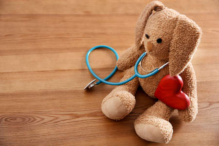 Toy bunny, stethoscope, heart and space for text on wooden background. Childrens doctor