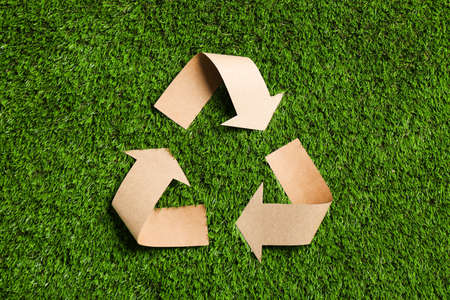 Recycling symbol cut out of kraft paper on green grass, top view Stok Fotoğraf
