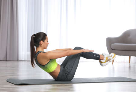 Young woman in fitness clothes doing exercise at home. Space for text Reklamní fotografie - 117420634