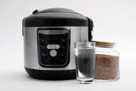 Modern electric multi cooker, buckwheat and glass of water on light background