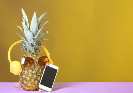 Pineapple with headphones, sunglasses and smartphone on table against color background. Space for text Stockfoto - 116163732