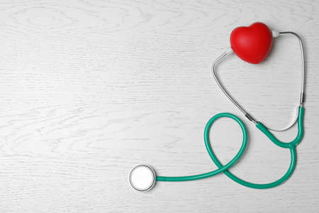 Stethoscope with red heart on white wooden background, flat lay. Space for text Foto de archivo