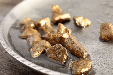 Plate with gold nuggets and water on table, closeup Stock Photo