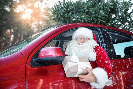 Authentic Santa Claus in car with gift box, view from outside