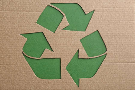 Sheet of cardboard with cutout recycling symbol on green background, top view