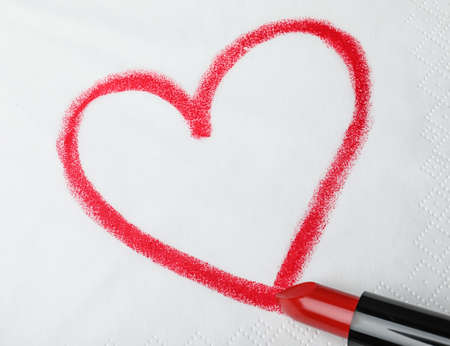 Drawing heart with lipstick on paper napkin, top view