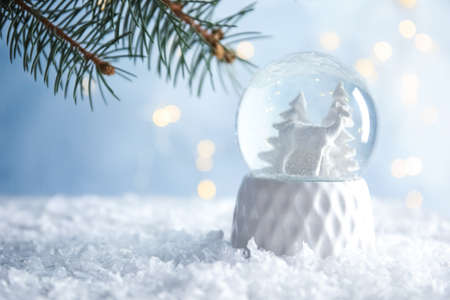 Glass globe with deer and trees on artificial snow. Space for text