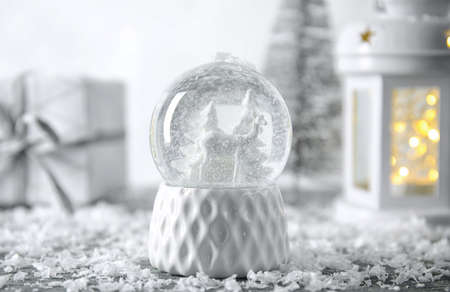Snow globe with Christmas decorations on table