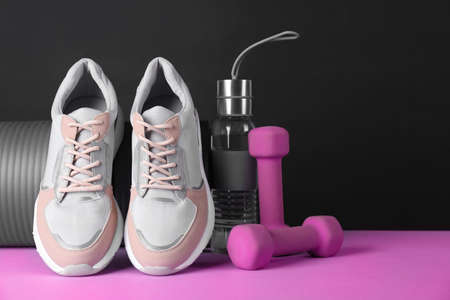 Composition of modern woman training shoes with mat, bottle and dumbbells on table. Space for text Фото со стока