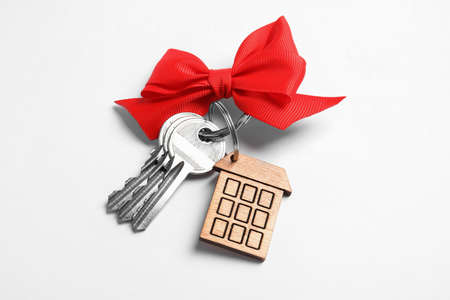 House keys with trinket and bow on white background Фото со стока