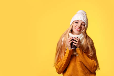 Portrait of young woman in stylish hat and sweater with paper coffee cup on color background, space for text. Winter atmosphere