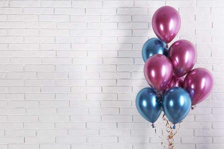 Globos de colores brillantes cerca de la pared de ladrillo, espacio para texto. Tiempo de fiesta