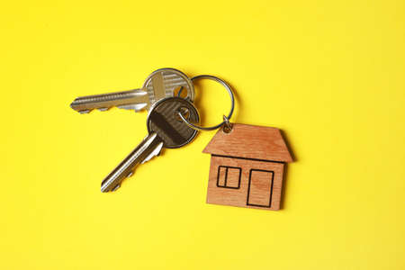 House keys with trinket on color background, top view Stock Photo