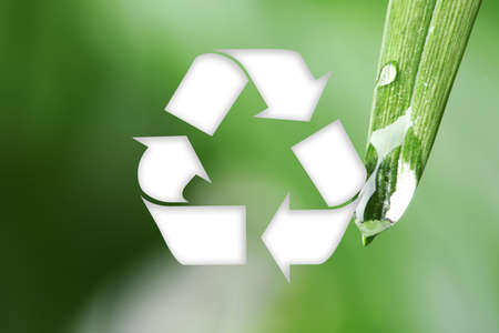 Symbol of recycling on blurred green background, closeup Banco de Imagens
