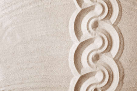 Zen garden pattern on sand as background, top view with space for text. Meditation and harmony Stock Photo
