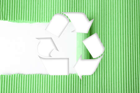 Symbol of recycling on green ripped corrugated cardboard background Archivio Fotografico