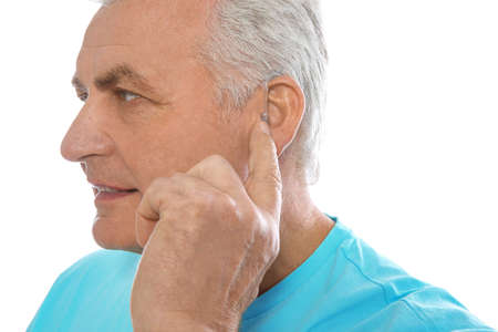 Mature man adjusting hearing aid on white background Stock Photo