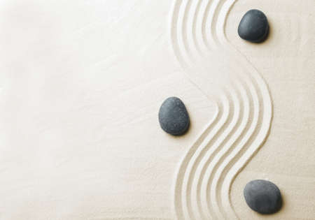 Zen garden stones on sand with pattern, top view. Space for text