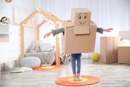 Cute little child wearing cardboard costume in bedroom