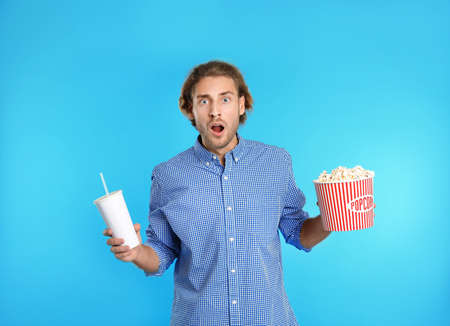 Emotional man with popcorn and beverage during cinema show on color background