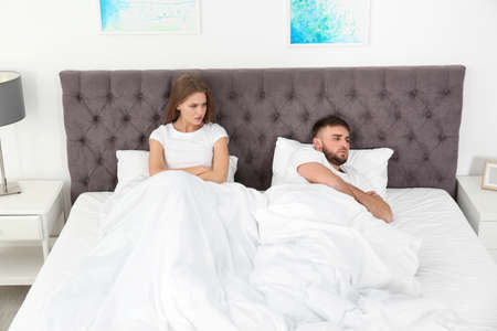 Upset young couple with relationship problems in bedroom