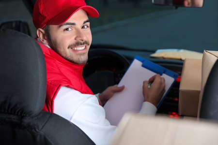 Deliveryman with clipboard and parcels in car Фото со стока