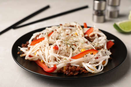 Plate with rice noodles, meat and vegetables on table