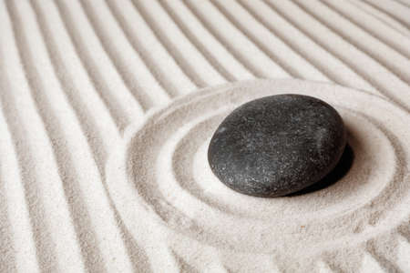 Zen garden stone on sand with pattern, space for text. Meditation and harmony Фото со стока
