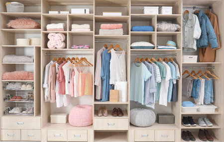 Stylish clothes, shoes and accessories in large wardrobe closet 版權商用圖片