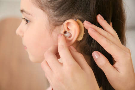 Young woman putting hearing aid in daughter's ear indoors, closeup Stockfoto