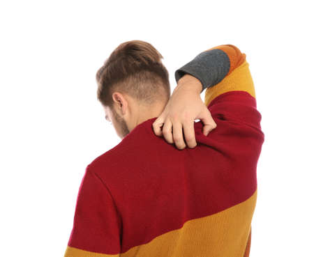 Young man scratching back on white background. Annoying itch Stock Photo