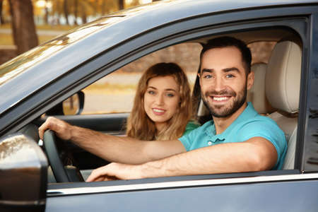 Young man sitting in car with passenger. Driving license test Foto de archivo