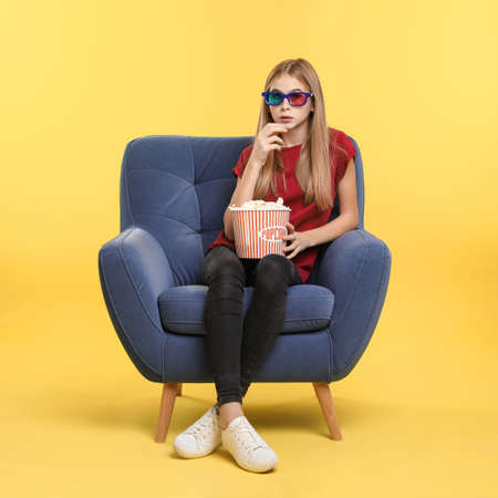 Emotional teenage girl with 3D glasses and popcorn sitting in armchair during cinema show on color background
