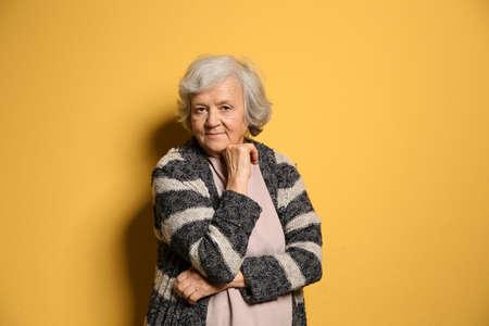 Portrait of elderly woman on color background Imagens