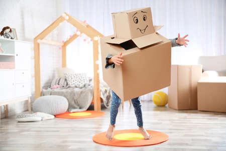 Mignon petit enfant portant un costume en carton dans la chambre