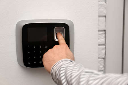Man scanning fingerprint on alarm system indoors, closeup