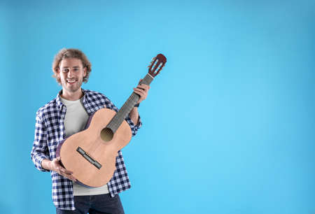 Young man with acoustic guitar on color background. Space for text
