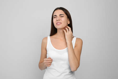 Young woman scratching neck on light background. Annoying itch Archivio Fotografico