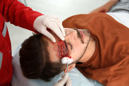 Nurse cleaning young mans head injury in clinic. First aid