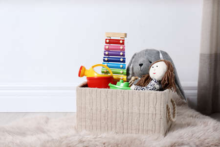 Box with different child toys on floor against white wall. Space for text Standard-Bild