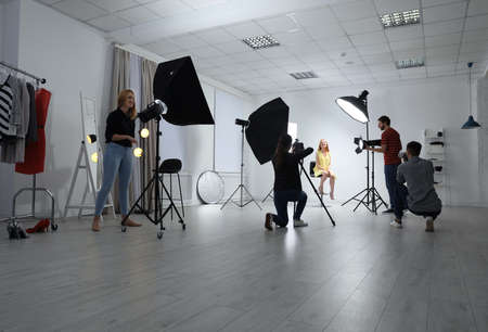 Photo studio with professional equipment and team of workers Imagens