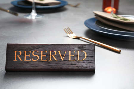 Table setting with RESERVED sign in restaurant. Space for text