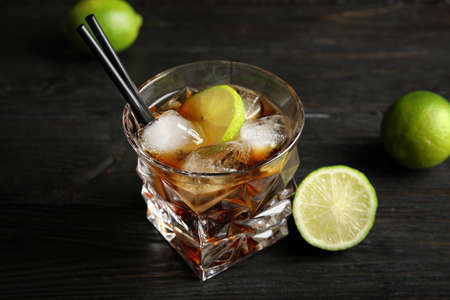 Glass of cocktail with cola, ice and cut lime on wooden background