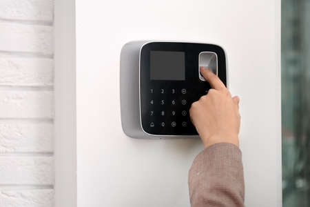 Woman scanning fingerprint on alarm system indoors, closeup