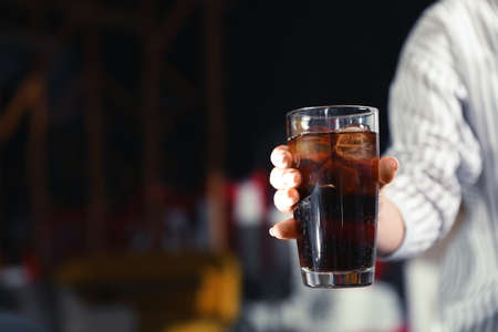 Woman with glass of refreshing cola indoors, closeup. Space for text