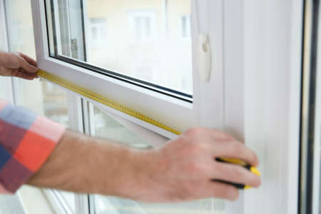 Construction worker measuring plastic window indoors, closeup. Professional installation