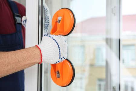 Trabajador de la construcción con elevador de succión durante la instalación de ventanas en interiores, primer plano